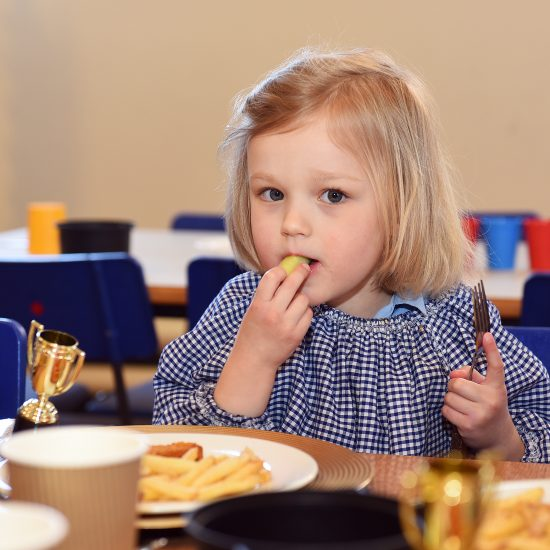 child eating school dinner with trophies on table