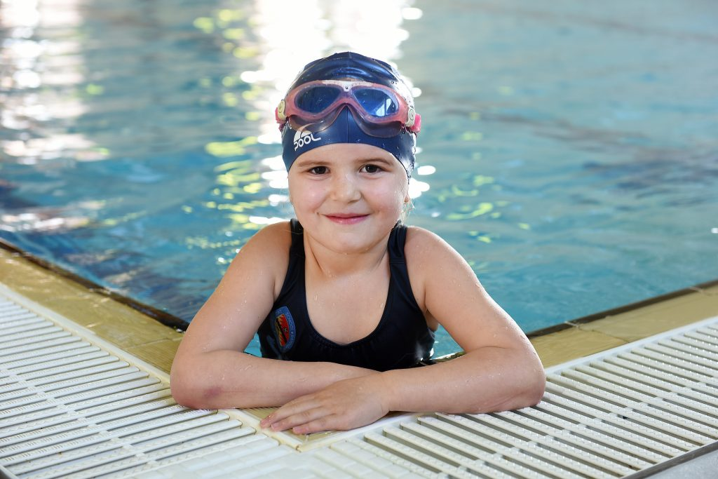 girl in swimming pool wearing a swimming hat and goggles